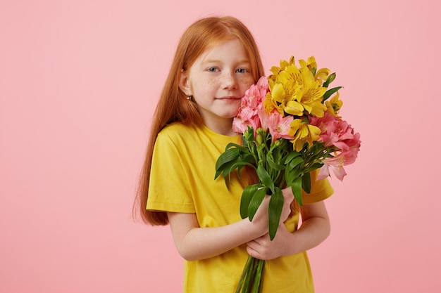 Portrait petite cute smiling freckles red-haired girl with two tails, holds bouquet, wears in yellow t-shirt, stands over pink background.