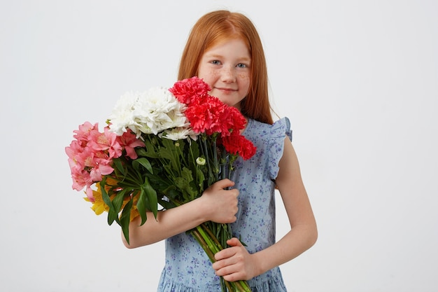 Free Photo Portrait Petite Freckles Red Haired Girl Smiling And Looks Cute Wears In Blue Dress Holds Bouquet And Stands Over White Background