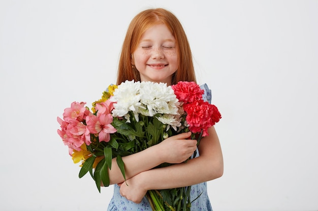 Portrait of petite freckles red-haired girl, with closed holds bouquet and enjoying the smell of flowers, and looks cute, wears in blue dress, stands over pink background.