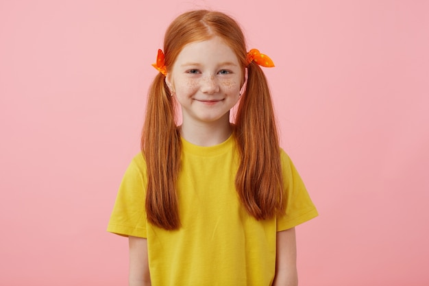 Portrait of petite freckles red-haired girl with two tails, looks into the camera and smiles, wears in yellow t-shirt, stands over pink background.