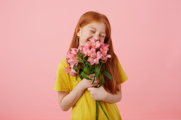 Portrait petite smiles freckles red-haired girl with two tails, looks cute, wears in yellow t-shirt, holds bouquet and stands over pink background, enjoying the smell of flowers.