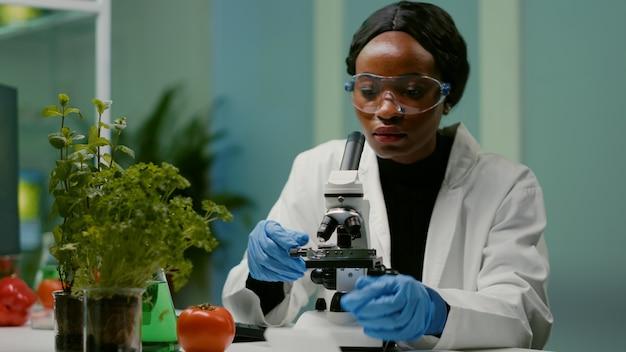 Ritratto di donna farmaceutica che mette il vetrino al microscopio
