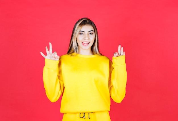 Foto ritratto del modello di ragazza attraente con la lingua fuori che mostra il gesto giusto