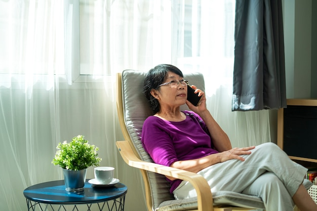 Portrait photo of elderly or old asian retirement woman smiling and talking on smartphone while siting on armchair in living room. technology, communication and people concept