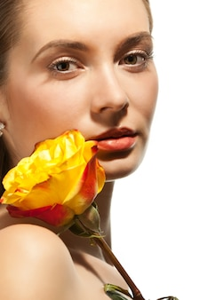 Портретная фотография девушки с каштановыми волосами, держащая красную и желтую розу возле ее плеча