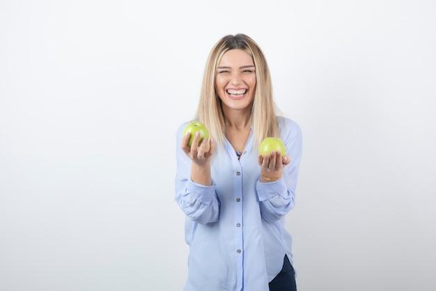 新鮮なリンゴを立って保持しているかなり魅力的な女性モデルのポートレート写真。