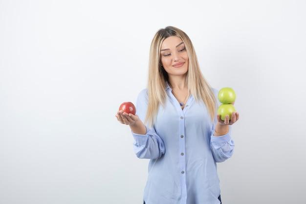 Фото портрета довольно привлекательной модели женщины стоя и держа свежие яблоки.