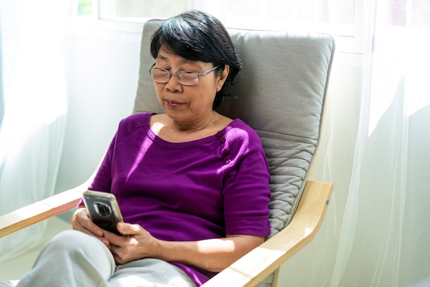 노인 또는 오래 된 아시아 은퇴 여자 웃 고 거실에서 안락의 자에 Siting 동안 소셜 미디어 확인을 위해 스마트 폰을 사용의 초상화 사진. 기술, 커뮤니케이션 및 사람들 개념 프리미엄 사진