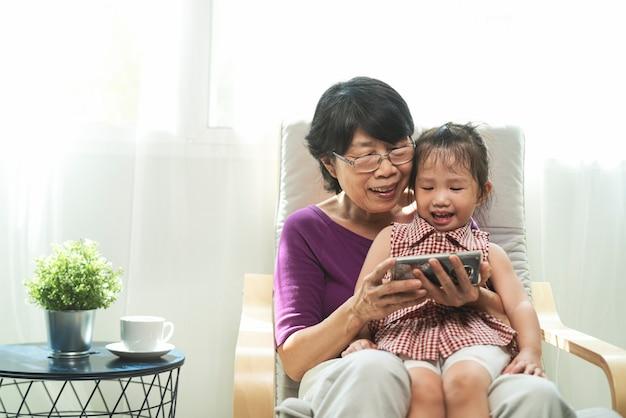 노인 또는 오래 된 아시아 은퇴 여자 웃 고 거실에서 안락의 자에 그녀의 손녀와 함께 siting 동안 스마트 폰보고의 초상화 사진. 기술, 커뮤니케이션 및 사람들 개념