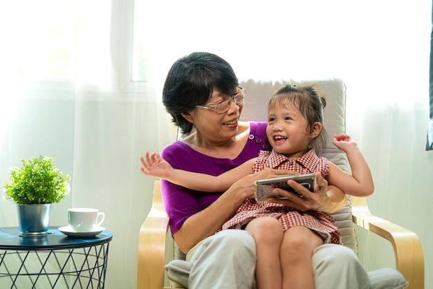 リビングルームの肘掛け椅子に彼女の孫娘と一緒に座っている間、スマートフォンで笑って見ている高齢者または古いアジアの退職女性の肖像写真
