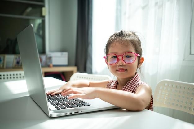 社会的距離のために自宅でホームスクーリングのためにラップトップコンピューターを使用している幼稚園の中国の女の子の肖像写真。ホームスクーリング、教育、オンライン学習またはコロナウイルスの概念