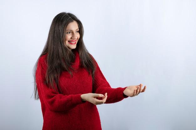 Foto ritratto di un modello positivo di giovane donna in maglione rosso caldo in piedi e in posa