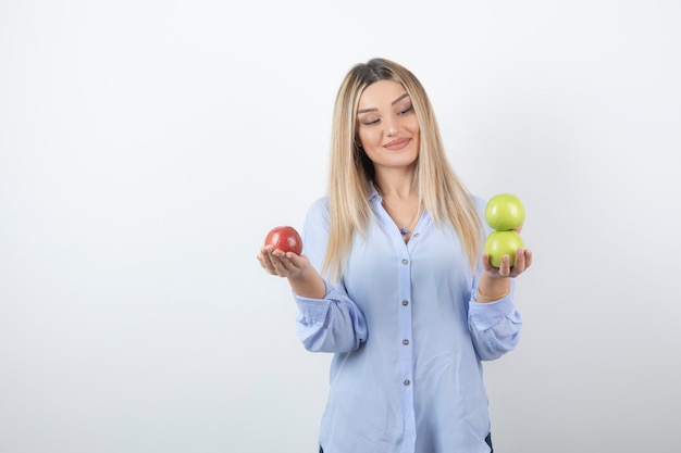 Portrait photo of a pretty attractive woman model standing and holding fresh apples .