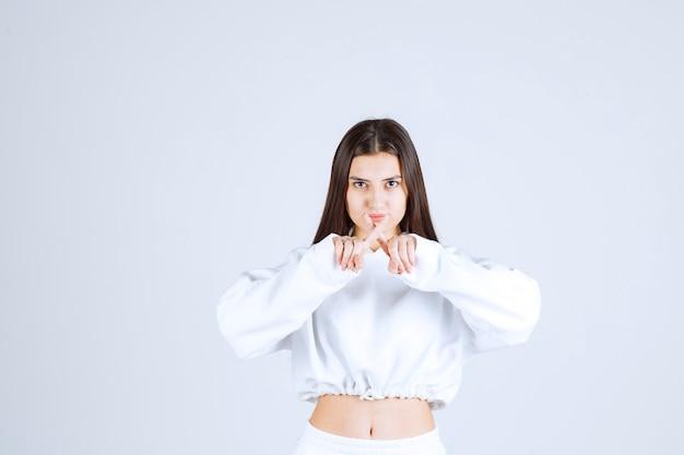 Foto ritratto di un modello di ragazza seria in piedi con le dita incrociate.