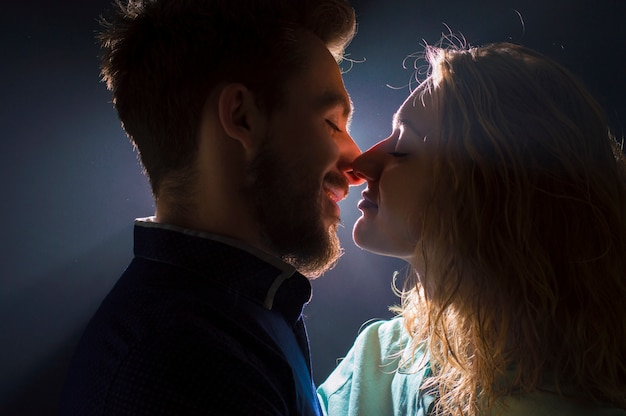 Portrait photo of a sexy young couple in pre kiss in streams of light