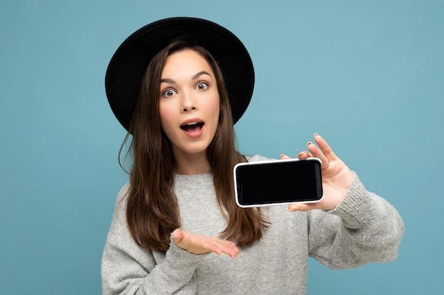 검은 모자와 회색 스웨터를 입고 아름다운 놀라운 젊은 여자의 초상화 사진 촬영