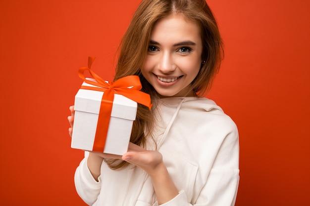 赤いリボンとスタイリッシュな白いギフトボックスを保持し、カメラを見ている白いパーカーを着てオレンジ色の背景の壁に分離されたかわいい笑顔のかわいい面白い金髪の若い女性の肖像写真のショット。