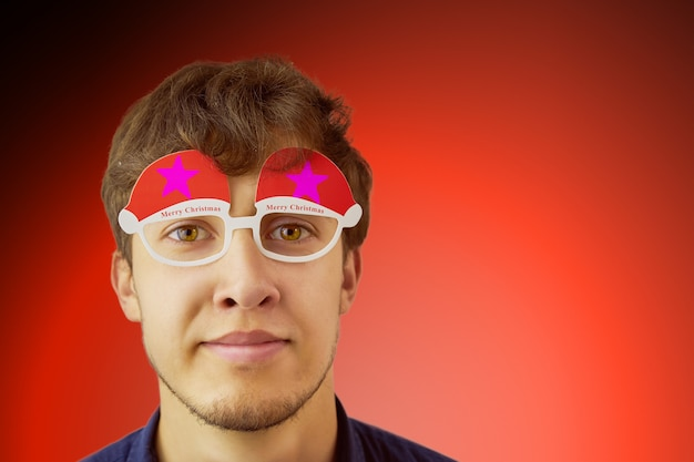 Portrait photo of smiling nerdy guy with christmas glasses on red background