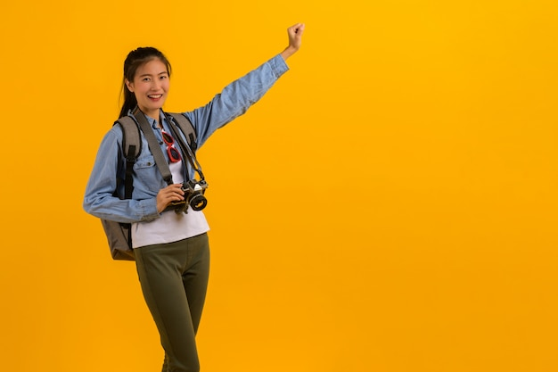 Portrait photo of young attractive asian tourist woman on yellow