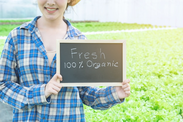 Portrait photo of young attractive beautiful asian woman harvesting fresh vegetable salad from her hydroponics farm hand hold blackboard with space for wording.