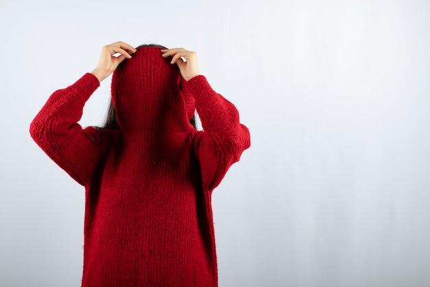Foto ritratto di una giovane modella con un maglione rosso caldo che copre il viso con il colletto