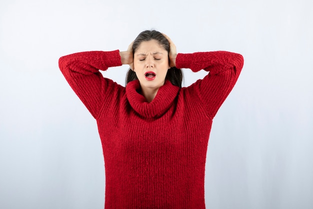 Foto ritratto di una giovane modella in maglione rosso caldo in piedi e in posa