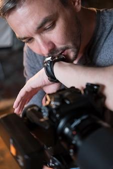Портрет фотографа и цифровой фотоаппарат крупным планом