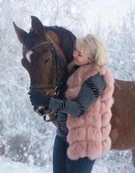 冬の背景に女性と馬のポートレート写真。