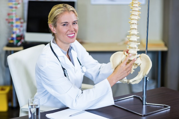 Portrait of physiotherapist holding a spine model