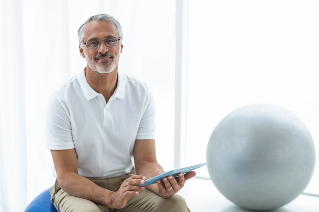 Portrait of physiotherapist sitting in exercise ball and using digital tablet at home