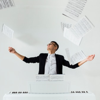 Portrait of a piano player throwing the musical sheets in the air sitting against the white background