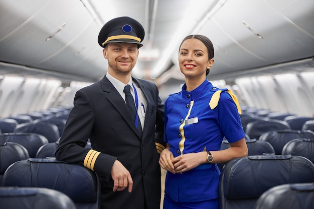 Portrait of pilot and stewardess in airplane salon before fly