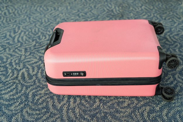 Portrait of pink trolley luggage suitable for light travels lying on carpet floor