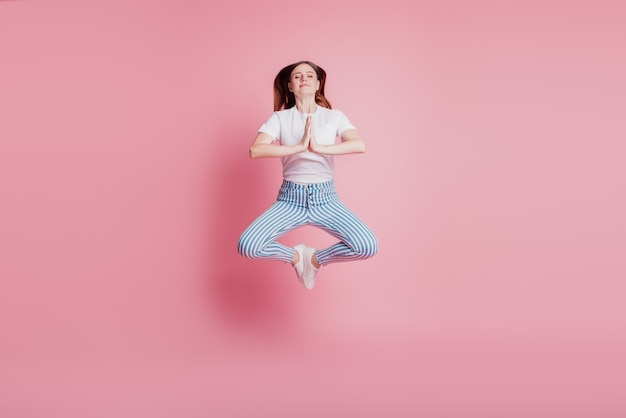 Portrait of playful crazy girl jumping in the air meditate lotus pose on pink background