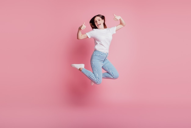 Portrait of playful crazy girl jumping in the air raise two thumbs up on pink background