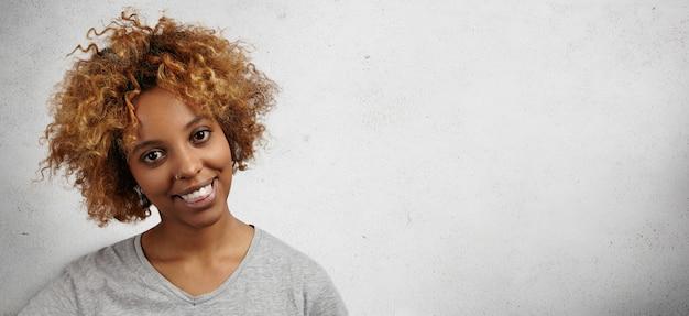 Ritratto di giocosa e divertente giovane studentessa dalla carnagione scura con taglio di capelli afro e anello nel naso che si morde la lingua mentre si diverte al chiuso dopo il college.