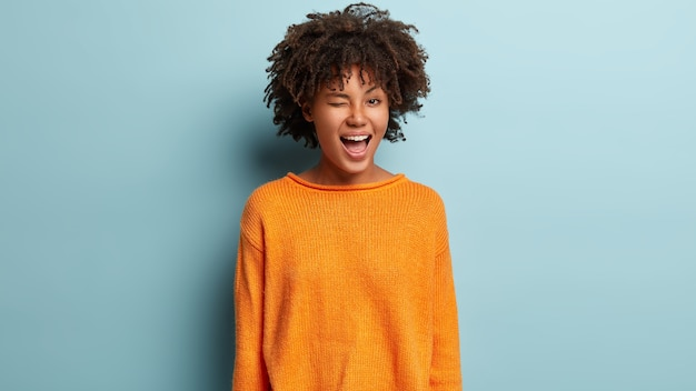 Portrait of playful funny young woman with glad expression, blinks eye, flirts with boyfriend, expresses good emotions, wears orange jumper, isolated over blue wall.