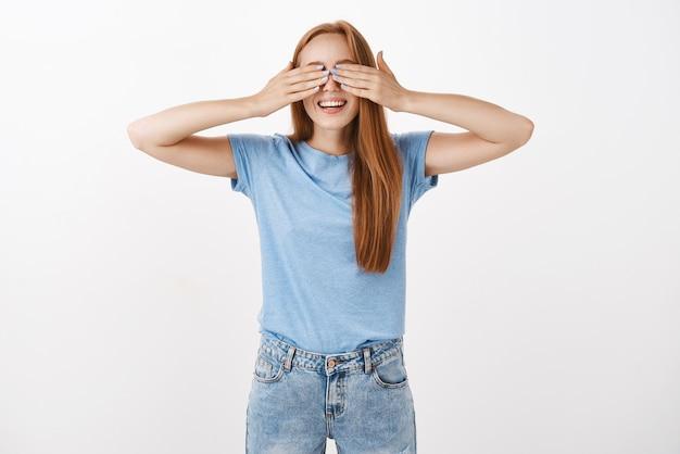 Ritratto di giovane ragazza giocosa e felice rossa in maglietta casual blu che copre gli occhi con le palme e sorridente mentre gioca a nascondino