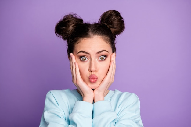 Portrait of playful lovely girl youth want comic her boyfriend on valentine day send air kiss touch hands face wear trendy clothes isolated over violet color background