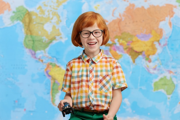 Portrait of playful red haired little boy in colorful clothes, holding toy car in hands, having good mood while going to kindergarten. funny redhead boy posing against world map. children and school