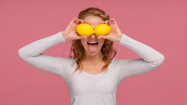 Portrait playful woman holding lemons and laughs