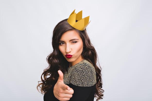 楽しい黄色い王冠の肖像画遊び心のある女性。興奮した若い素晴らしい女性、豪華な黒のドレス、長い巻き毛のブルネットの髪、真剣な感情。新年会、誕生日、演奏。
