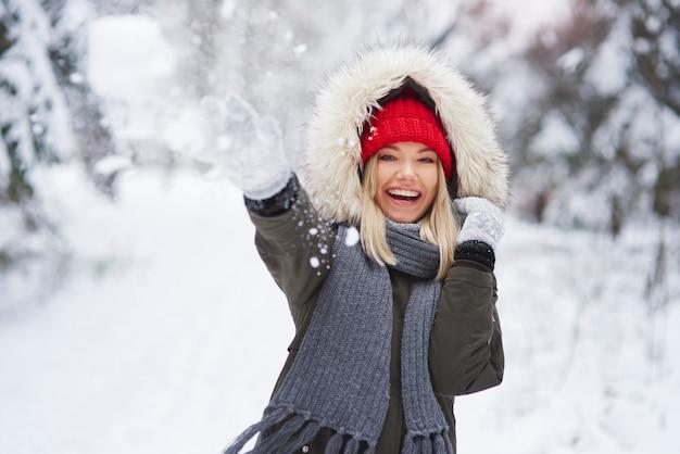 Ritratto di donna allegra che lancia palle di neve