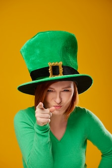 Portrait of playful woman with leprechaun's hat pointing at camera