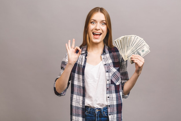 Portrait of a playful young woman with long hair holding bunch of money banknotes and looking at camera. ok sign.