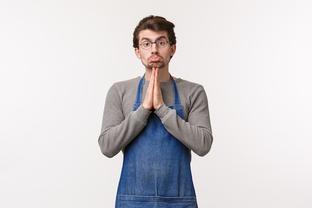 Portrait of pleading cute silly caucasian man in apron, coffee shop employee asking coworker cover him at work, need go home early, say please with hands in pray,