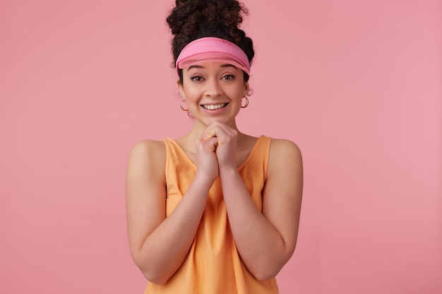 Portrait of pleading girl with dark curly hair bun. wearing pink visor, earrings and orange tank top. has make up. keeps palms together