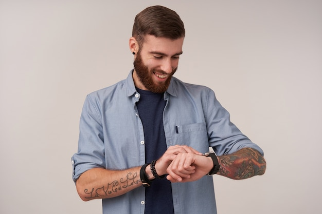 Portrait of pleasant looking positive bearded man with short haircut standing on white and setting time on his hand watch, being in good mood