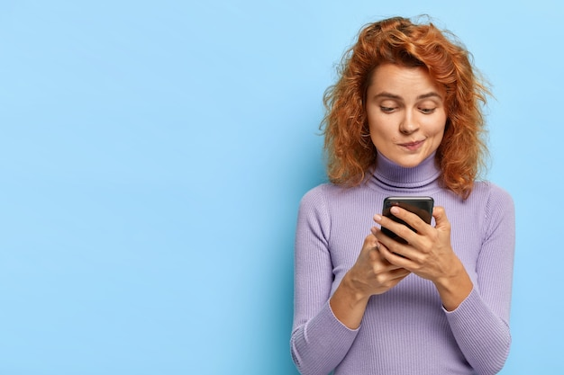 Portrait of pleasant looking redhead lady focused in smartphone device, checks email box, chats online