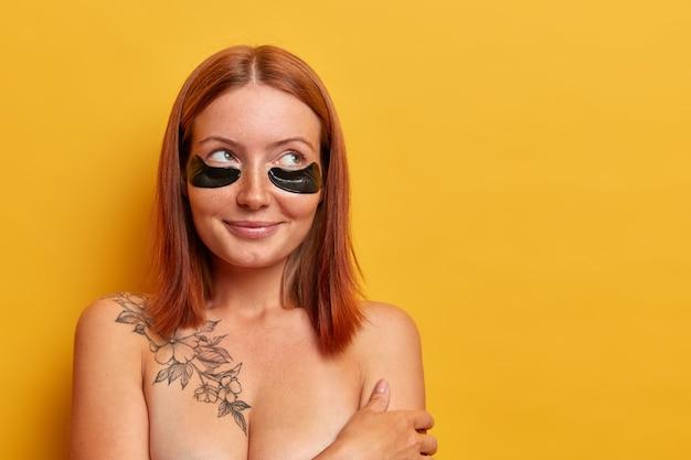 Il ritratto di una donna dai capelli rossi dall'aspetto piacevole applica le toppe per ridurre il gonfiore degli occhi e le occhiaie, ha un sorriso affascinante, sta a torso nudo contro il muro giallo. bellezza e ringiovanimento